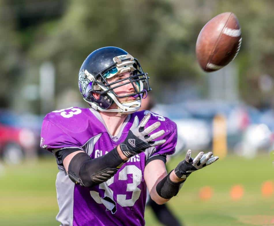 Football wide receiver in purple puts his arms out to catch the football.