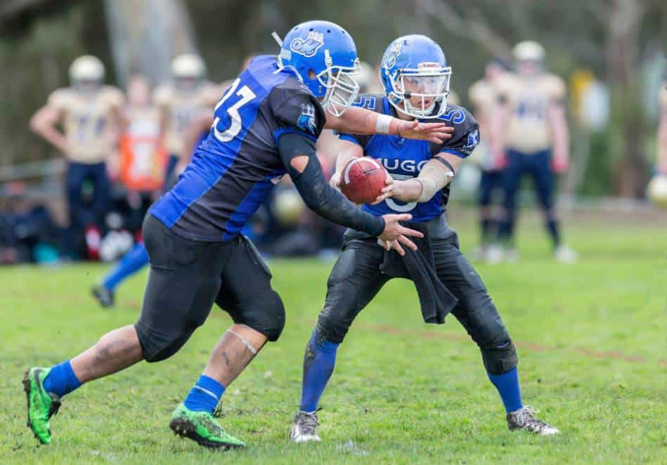 Youth football quarterback in blue runs play action.
