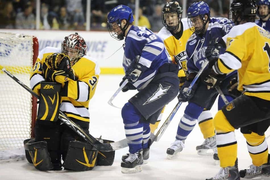 Hockey goalie secures the puck against himself.