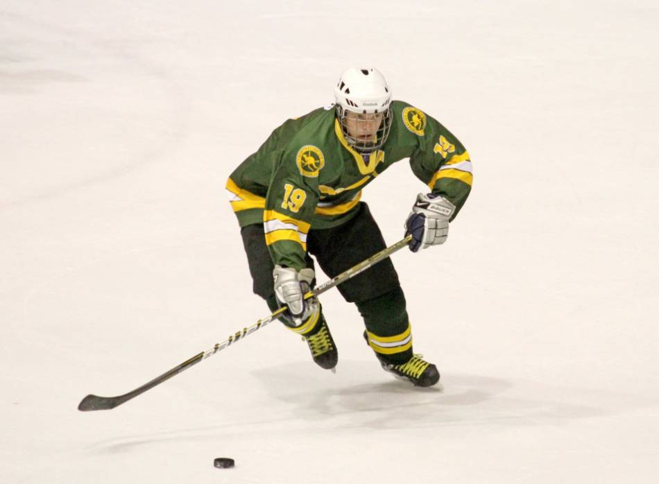 Hockey player in a green and yellow jersey skates with the puck.