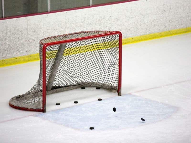 Hockey net full of hockey pucks.