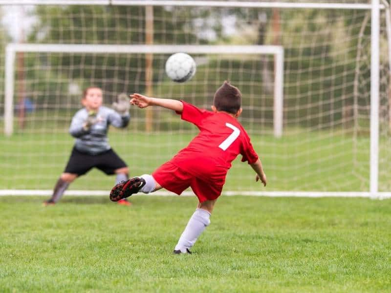 Youth soccer player in red jersey shoots soccer ball at net.