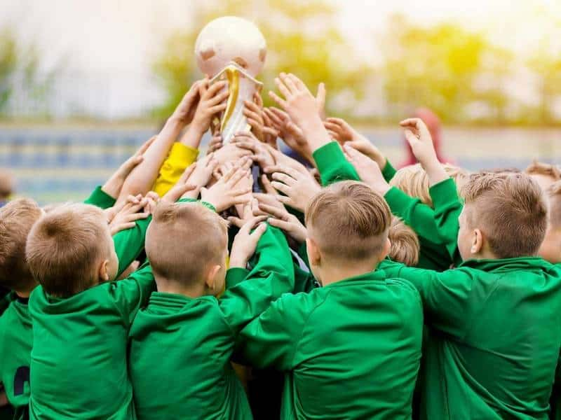 Youth soccer team holds up trophy.
