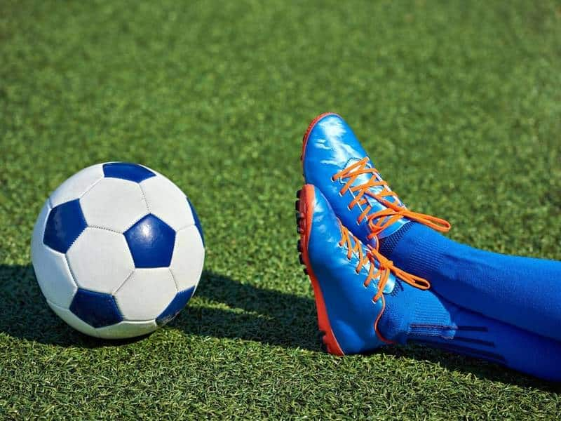 Soccer player with cleats sits next to soccer ball.