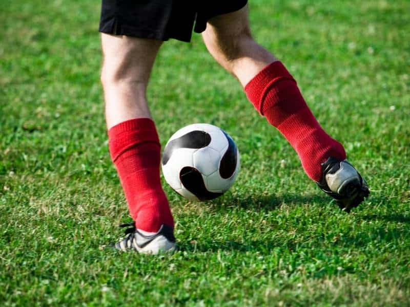 Youth soccer player with red socks dribble soccer ball.