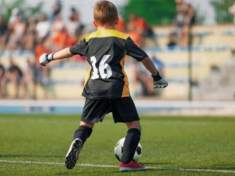 Youth soccer goalie kicking the ball.