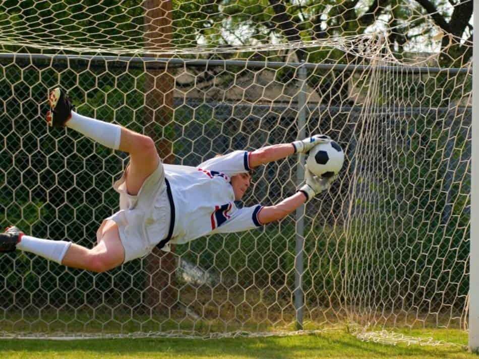Soccer goalie catches soccer ball during shootout.