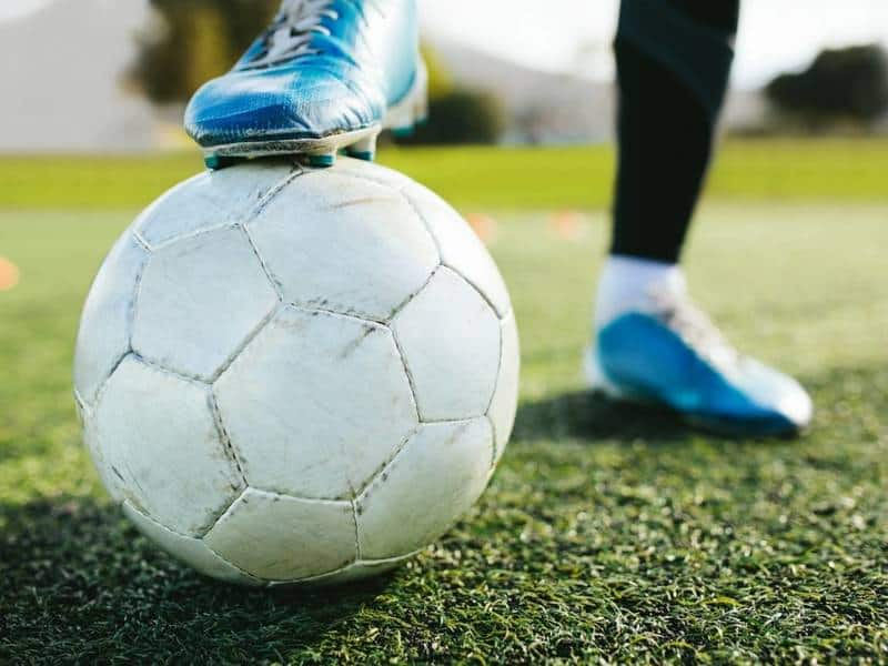 Soccer play with blue cleats stops soccer ball.