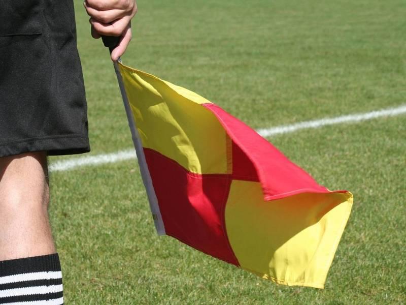 Soccer lineman holds flag.