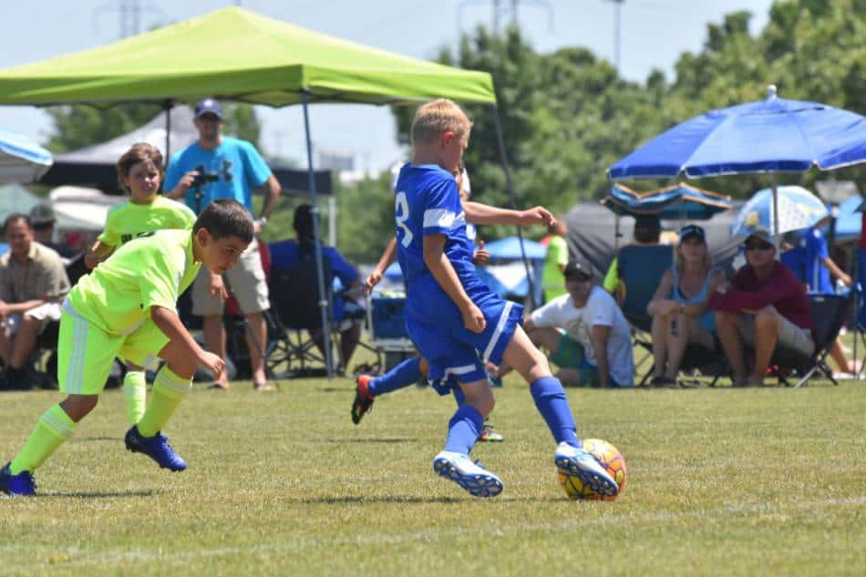Youth soccer player in blue passes to his teammate, while the team in neon green looks to intercept it.