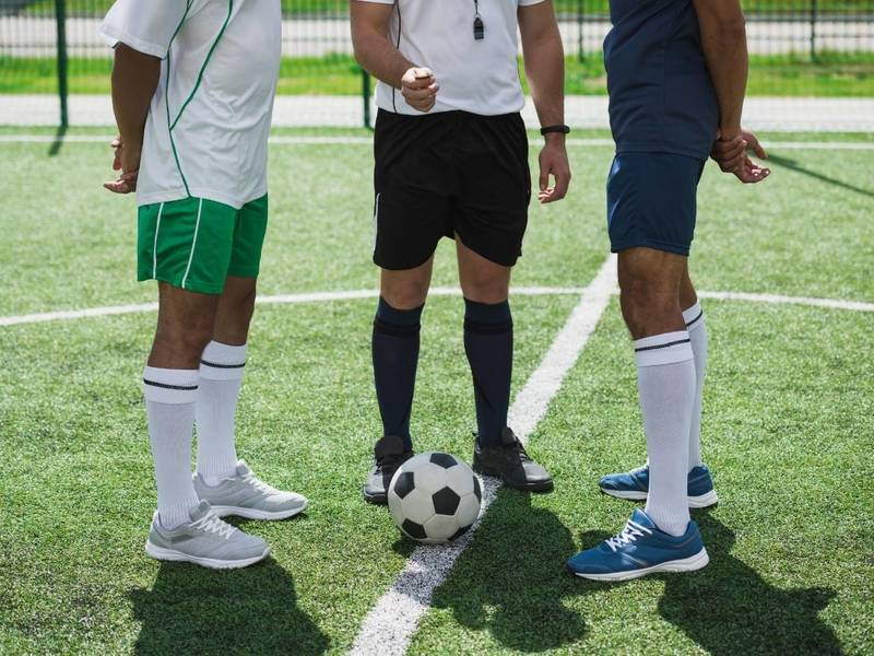 Soccer referee flips coin in front of two players.