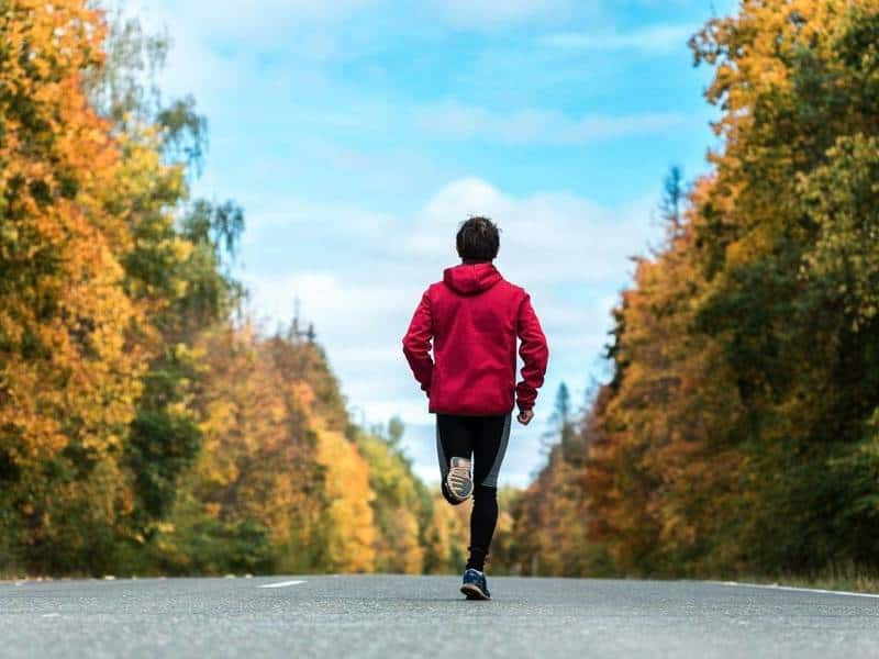 Man in red hoodie runs on a paved road.