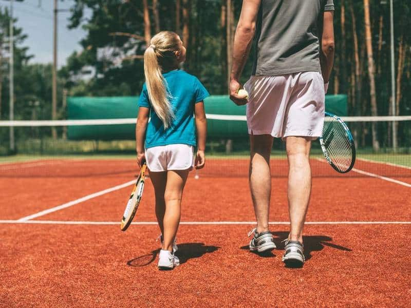 Young girl and man holding tennis rackets on tennis court.