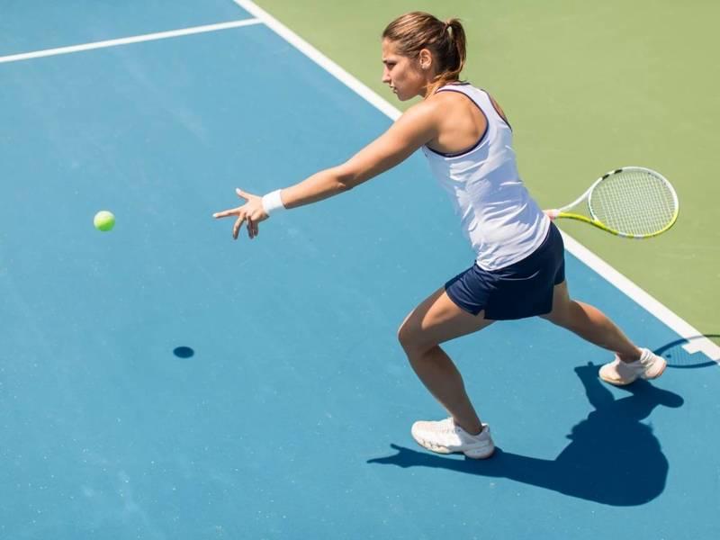 Tennis player prepares to hit tennis ball.