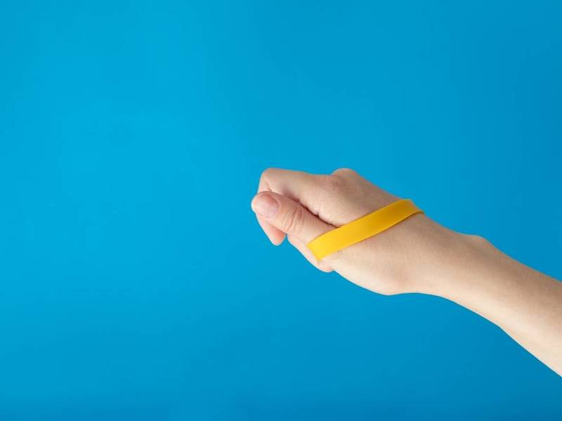 Person holds silicone wristband.