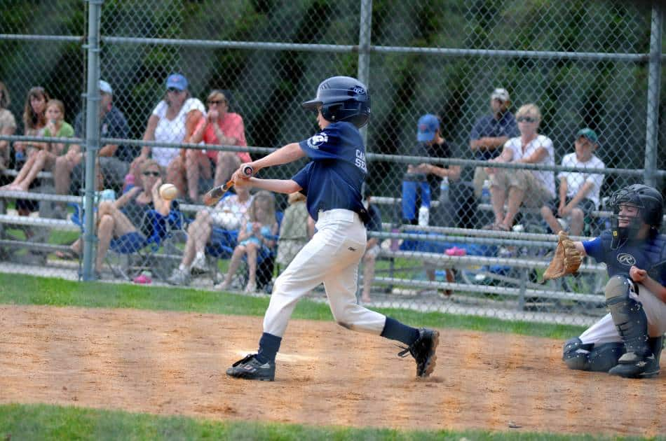 Little League baseball player makes contact with a pitch.