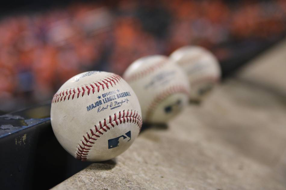 Three baseballs sitting along concrete steps.