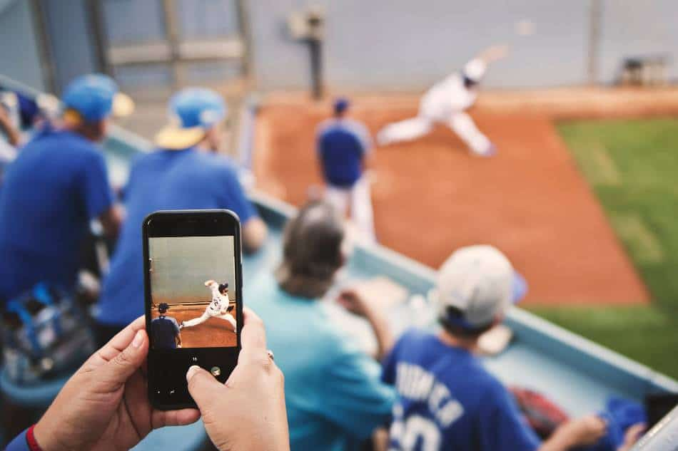 A fan films a Los Angeles Dodgers pitcher throwing in the bullpen with their phone.