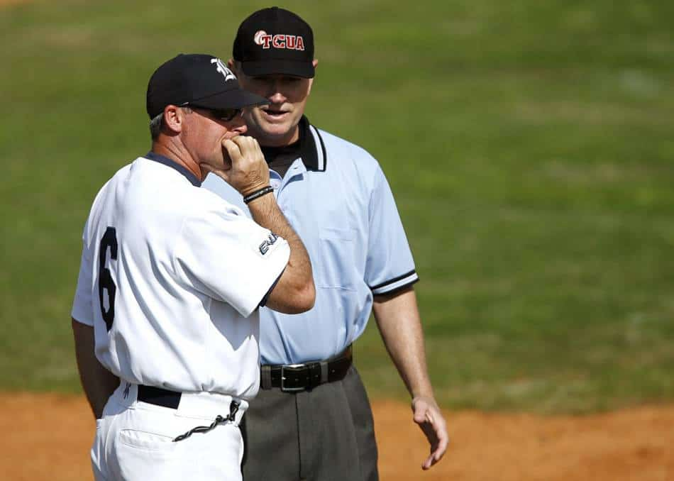 College baseball coach and umpire have a discussion.