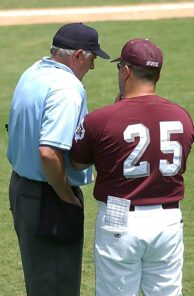 College baseball coach talks to one of the umpires.