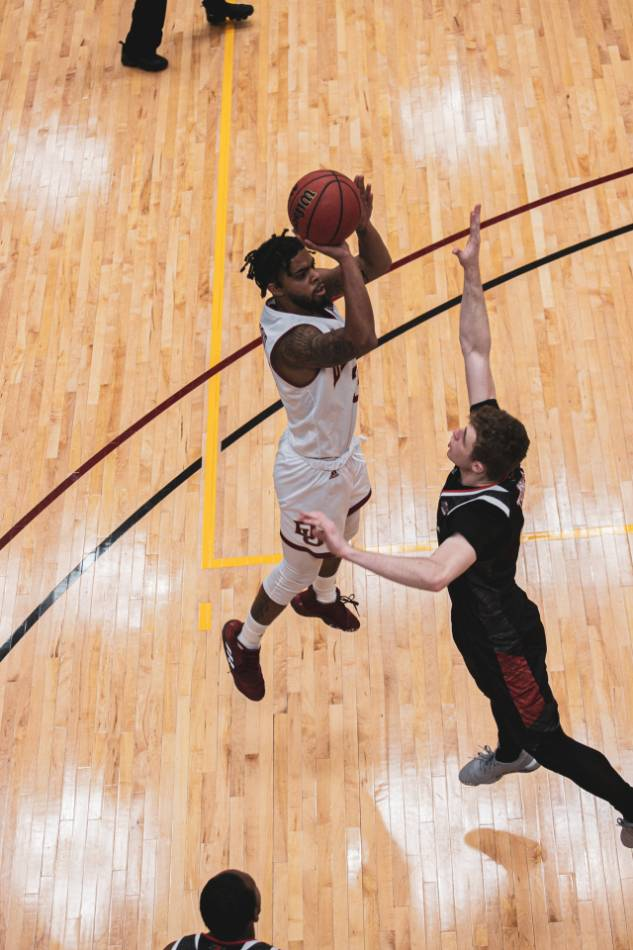 College basketball player in a white jersey shoots over a defending player in a black jersey.