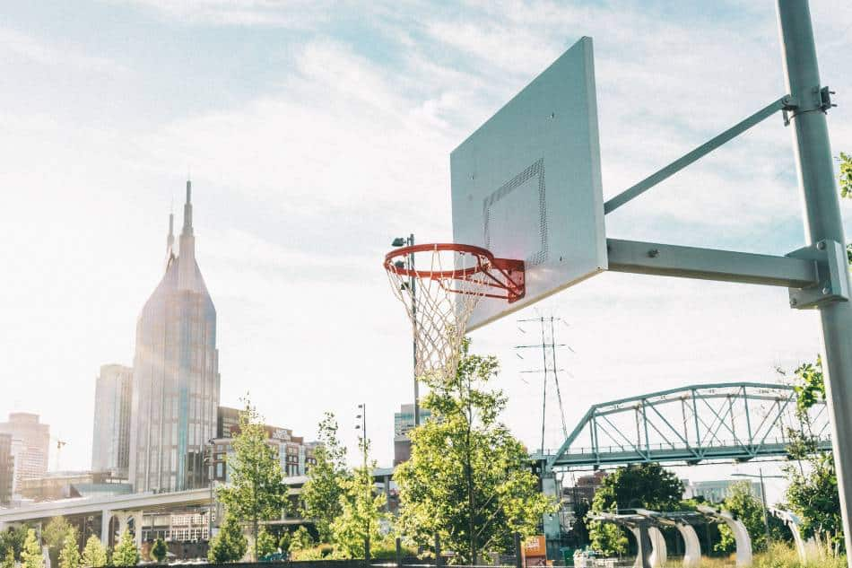 Basketball hoop at the park with city skyline in the background.