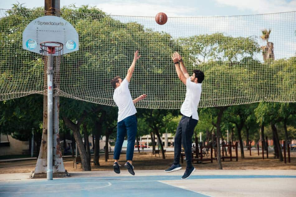 Man in a white shirt shooting a basketball over another man in a white shirt at a park.