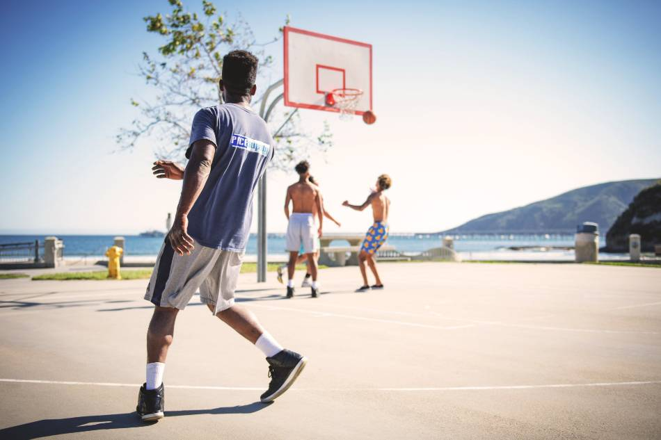 Four men playing basketball near the ocean.