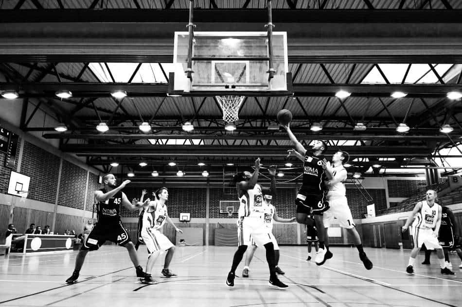Black and white photo of men playing basketball inside a gym.