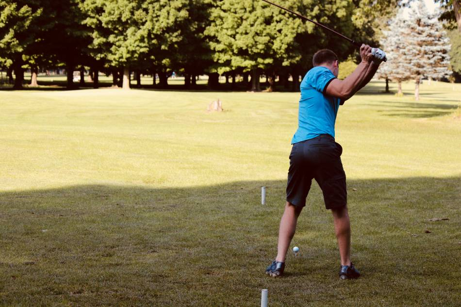 Golfer in light blue shirt prepares to hit the ball at the golf range.