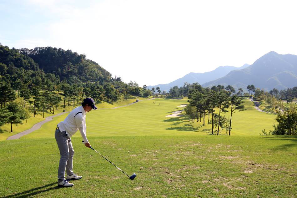 Golfer in a white shirt prepares to tee off.