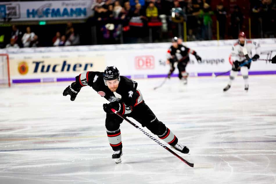 Hockey player in a black jersey skates as fast as he can.