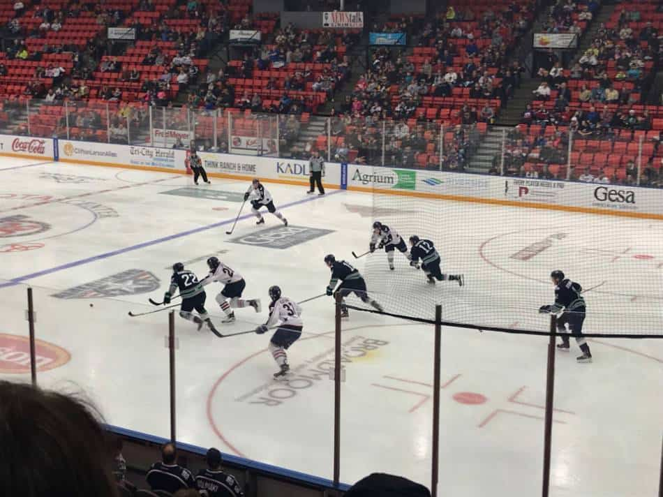 Both hockey teams race after the puck.