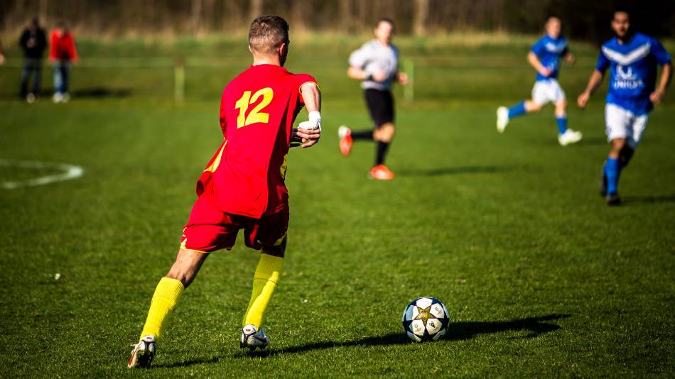 Soccer player in red and yellow looks to pass the ball.