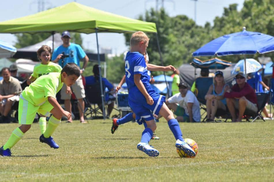 Youth soccer player in blue passes the ball to his teammates.