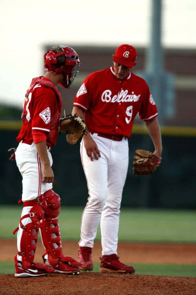 Pitcher and catcher in red jerseys meet at the mound.