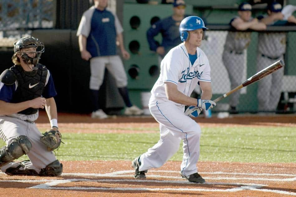 Baseball batter in white jersey with blue helmet puts the ball in play.