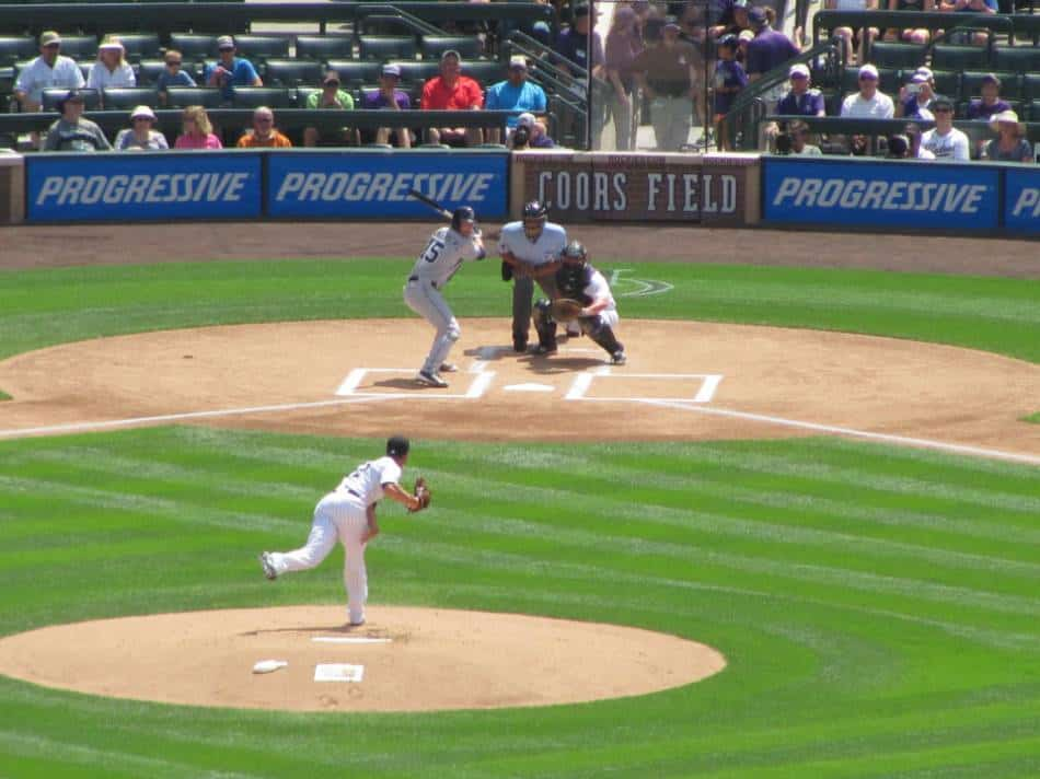 Left-handed baseball pitcher throws home at Coors Field.