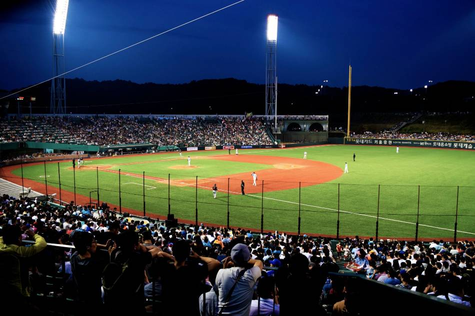 Baseball game with fans at night.