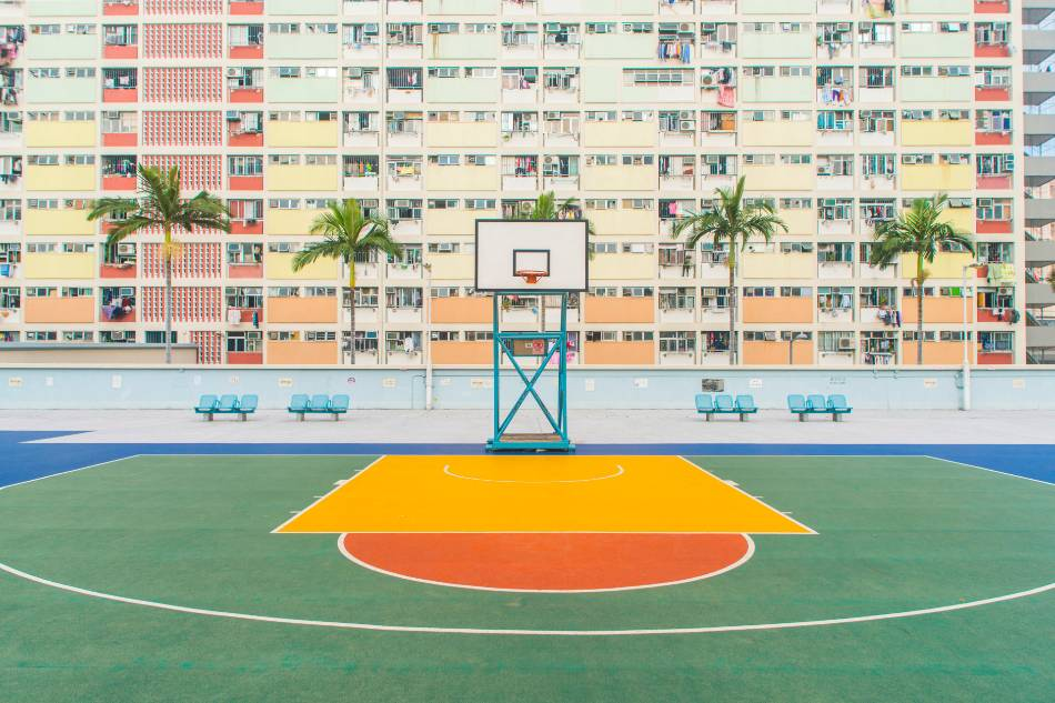 Basketball court with a hotel in the background.