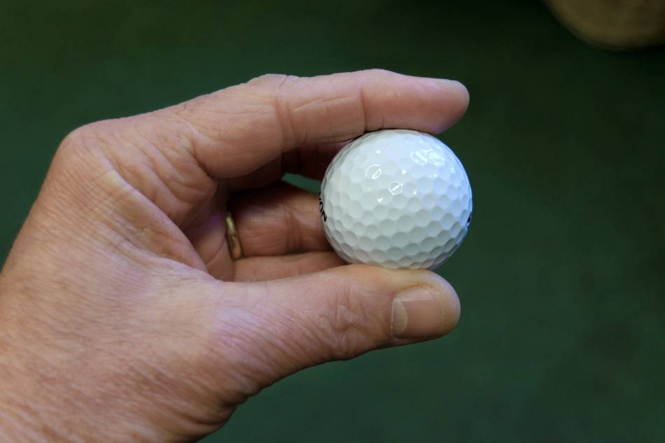 Man holds white golf ball between his fingers.