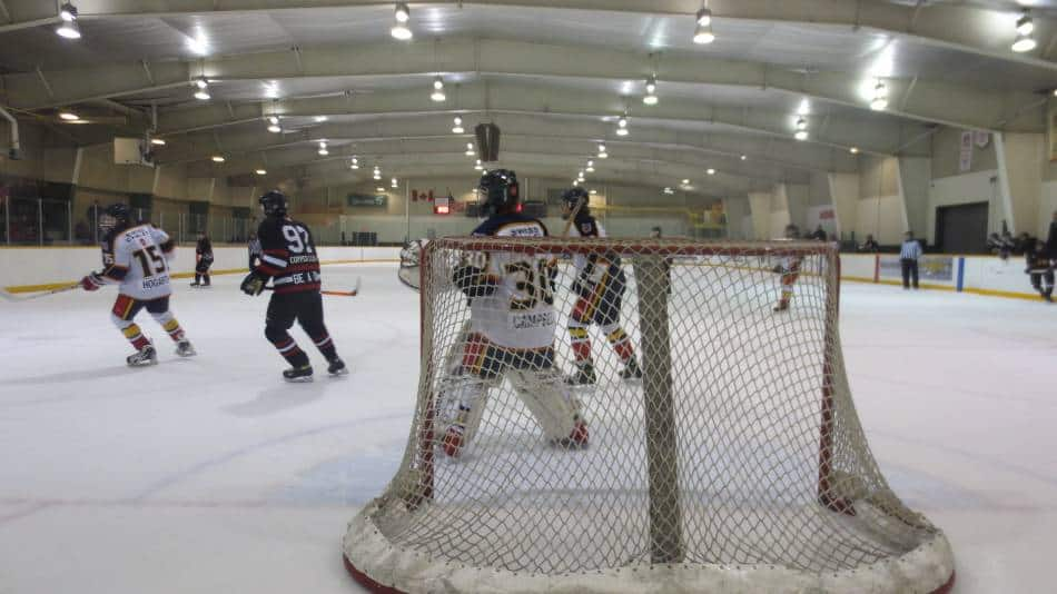 Hockey goalie positioning themselves to block the puck.