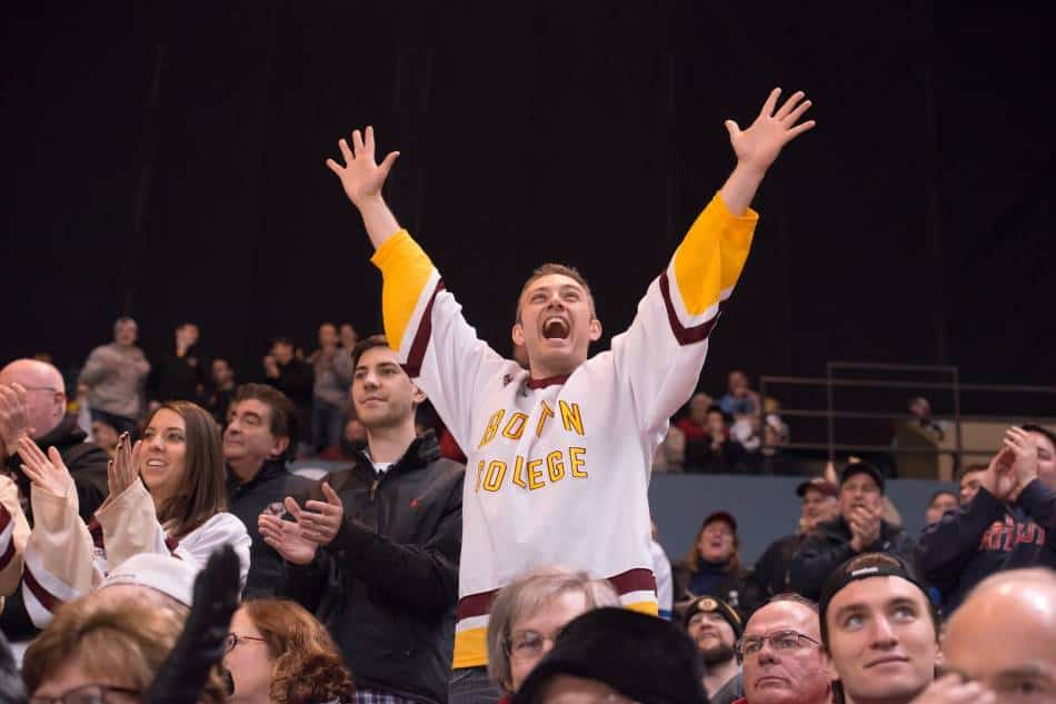 A Boston College hockey fan cheers in the crowd.