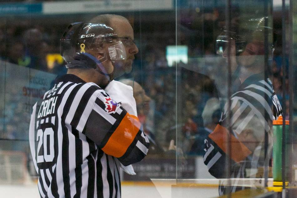 Hockey referees wipe their faces and drink water during an official's timeout.