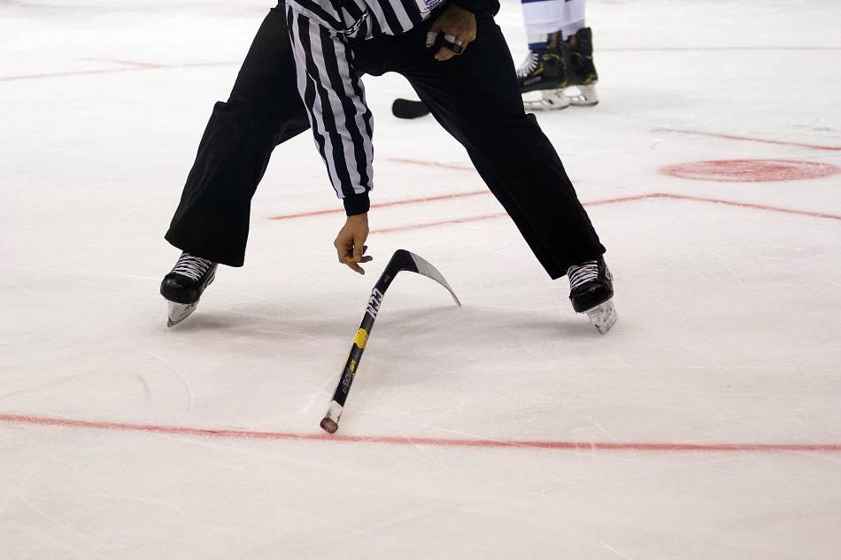 Hockey referee skates by during a game to pick up a broken stick.