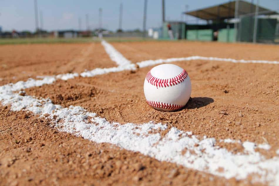 Baseball sitting in the dirt of the batter's box.