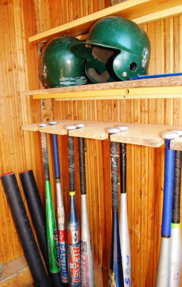 Wooden shed full of baseball bats and helmets.