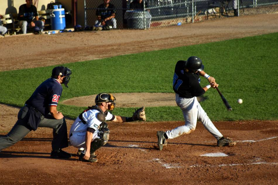 College baseball player in black squares up a pitch from the pitcher.