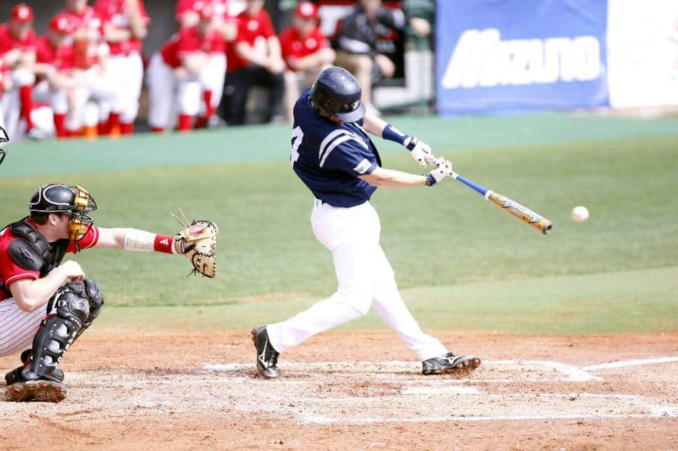 College baseball player hits a pitch with his aluminum bat.