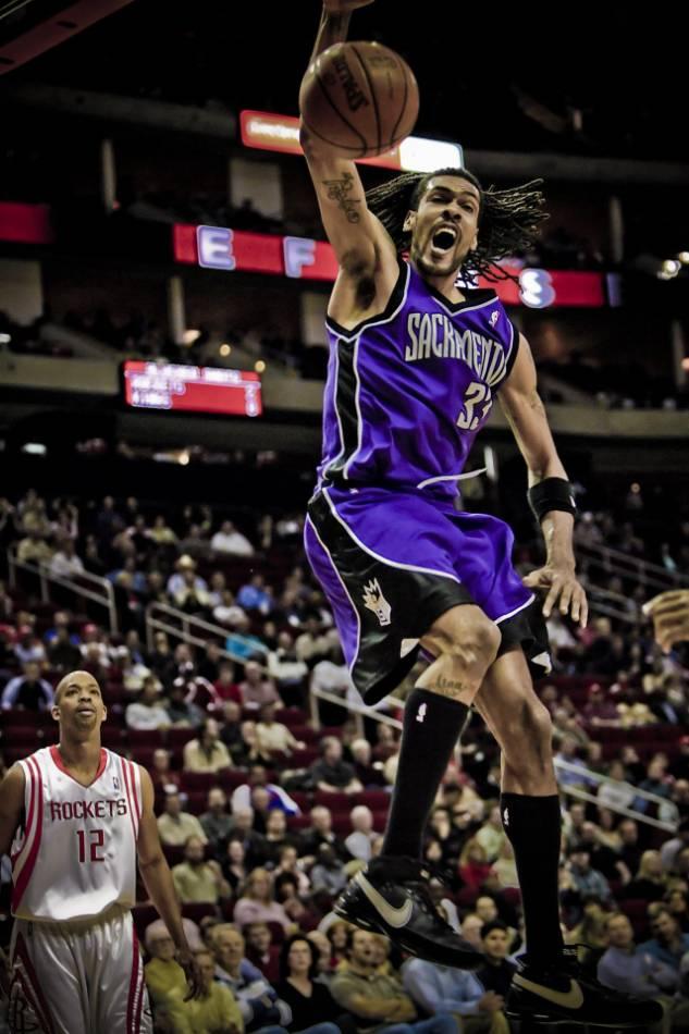 Sacramento Kings NBA player dunks the basketball.